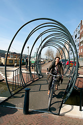 Cyclist crossing modern steel footbridge across canal in Java Island district of Amsterdam in The Netherlands
