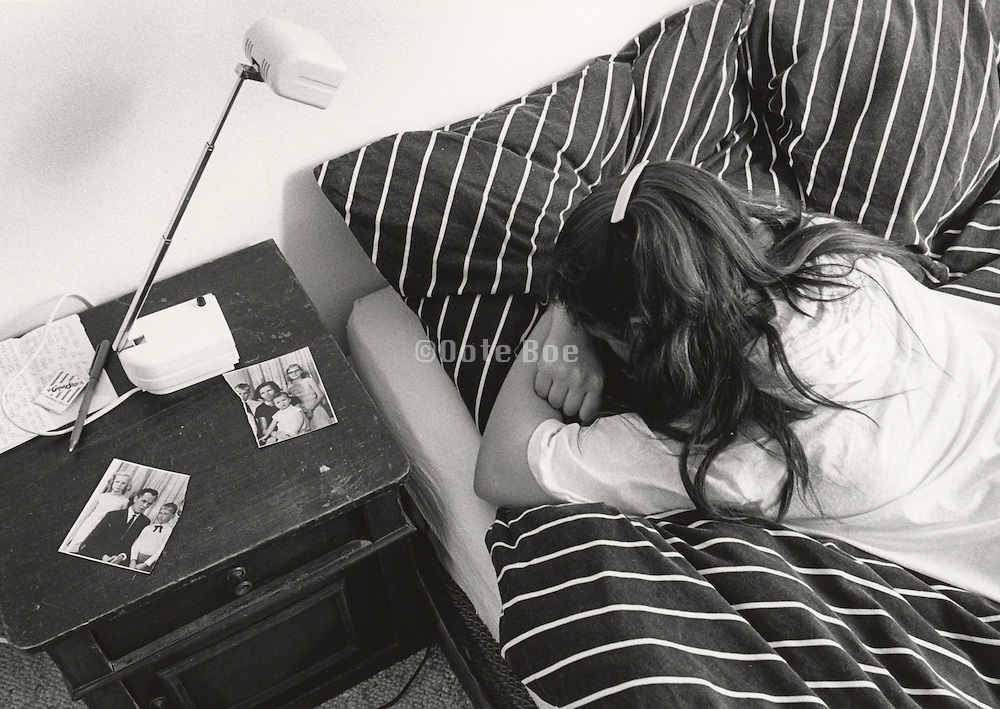 girl with head in hands on bed