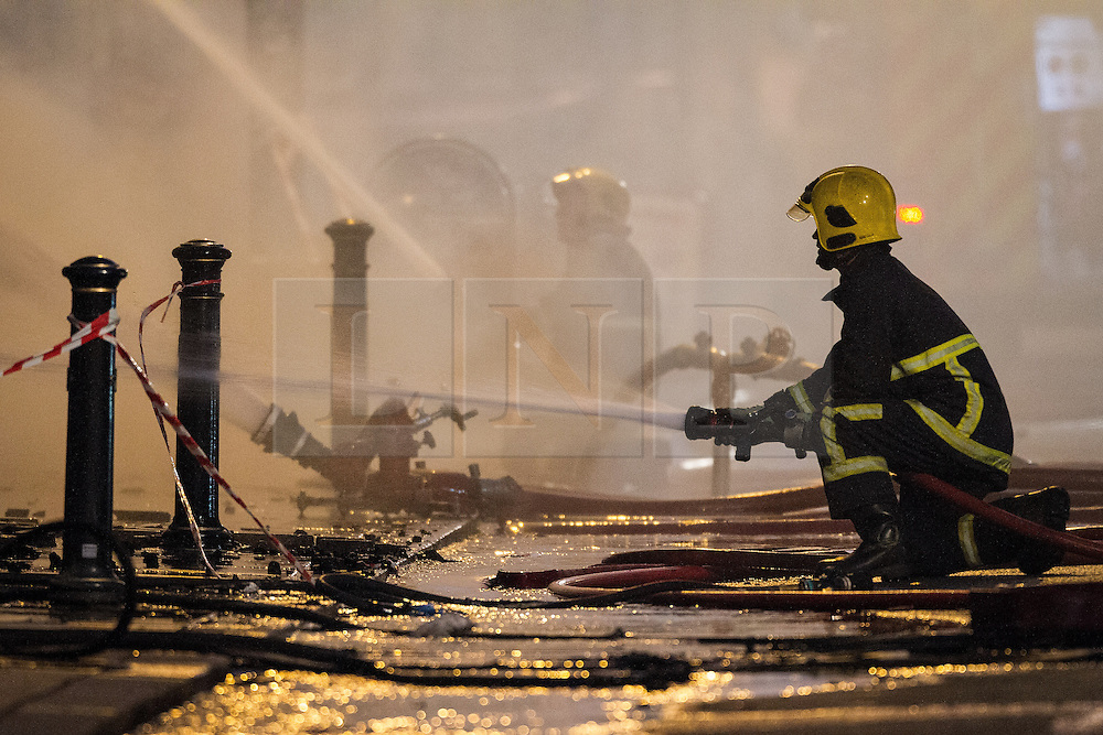 © Licensed to London News Pictures . 13/07/2013 . Manchester , UK . Fire crew work to quell the fire . A fire fighter is dead and two 15 year old girls are under arrest on suspicion of manslaughter after a blaze in Manchester yesterday (Saturday 13th July) . More than 60 fire fighters tackled a blaze at Paul's Hair World on Oldham Street in Manchester City Centre late in to the night (Saturday 13th July 2013) . Twelve crews from four stations were deployed . Several streets in a block in the city centre are sealed off . Photo credit : Joel Goodman/LNP