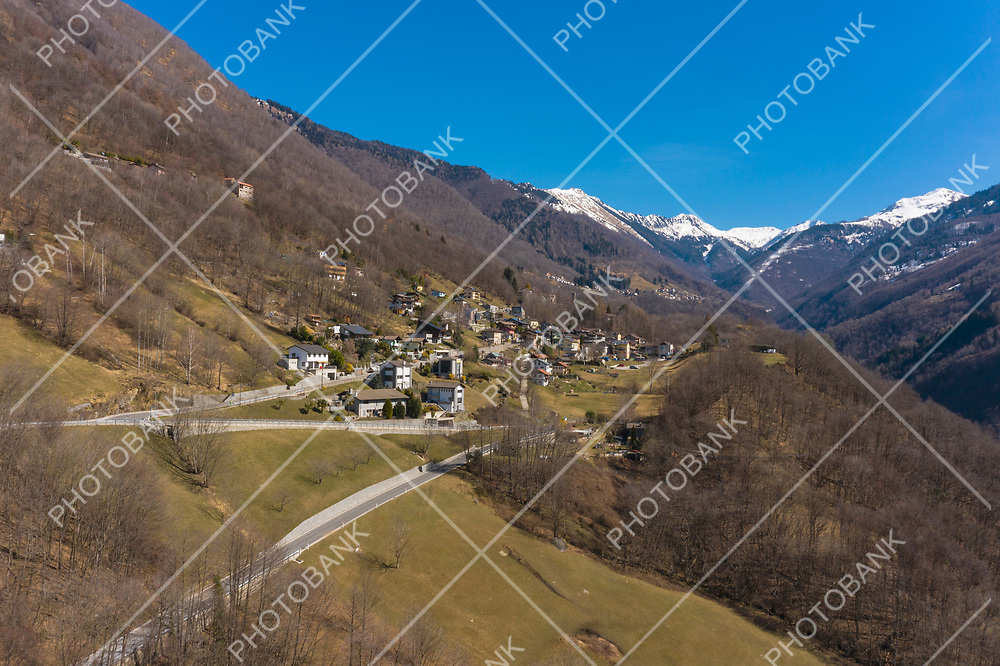 Aerial view of the Morobbia Valley, winter landscape on a sunny day with snow on the mountains. Blue sky