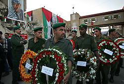 Palestinian security forces carry wreaths sent by foreign consulates and dignitaries, at the burial of Yasser Arafat inside his compound, Ramallah, Palestinian Territories, Nov. 12, 2004. Arafat died in a Paris hospital at the age of 75.