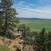 A hiker looks over a valley called The Big Sag in the Upper Missouri River Breaks of central Montana.