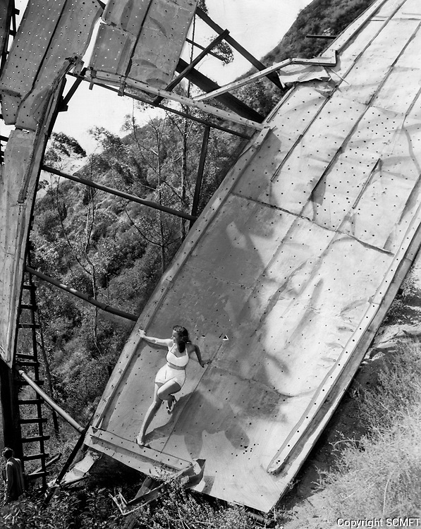 """April 1947 Singer Jane Webb poses on the letter """"H"""" of the Hollywoodland sign. The letter was blown down by a severe windstorm in March 1944."""