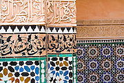 Detail of tile mosaics, stucco plasterwork and Islamic scripture on a wall inside the Ali ben Youssef Medersa in the Marrakech medina, Morocco