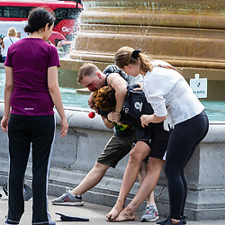 """A woman looks on helplessly as another tries to get two men fighting, the one an alleged pickpocket, held in a headlock by a fellow Romanian, a street performer, after street performers demanded that Romanian pickpockets desist from """"working"""" on the North Terrace of Trafalgar Square where they steal from crowds watching the street entertainers. London, August 02 2019."""