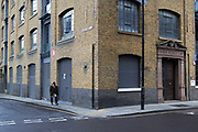 Muslim man walking past an old warehouse building in Whitechapel in London, England, United Kingdom. This area feels very much like old London and has a healthy Bangladeshi community. A quiet corner in an industrial setting.