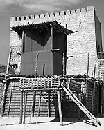 A black and white image of Al Manama Summer Bed and House with Cooling Tower in Dubai. This is a traditional style of house lived in by the local Emirate Dubai population before its period of modernisation. The house shows the traditional cooling tower used before the days of air-conditioning and next to the wood a reed structure we see an Al Manama or summer bed. This was a simple wooden platform built high above the sand and used for sleeping during the hot summer nights where temperatures can reach as high as fifty degrees celcius.