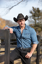 Rugged good looking cowboy leaning on a wooden fence