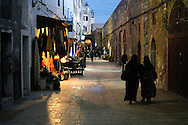 Morocco, Essaouira. Two women walking in the street of the medina in the evening.