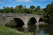 Bridge over the River Teme towards Ludlow Castle on 6th June 2021 in Ludlow, United Kingdom. Ludlow is a market town in Shropshire, England. With a population of approximately 11,000, Ludlow is the largest town in south Shropshire. The town is near the confluence of two rivers. The oldest part is the medieval walled town, founded in the late 11th century after the Norman conquest of England. It is centred on a small hill which lies on the eastern bank of a bend of the River Teme. Atop this hill is Ludlow Castle and the parish church, St Laurences, the largest in the county. From there the streets slope downward to the River Teme.
