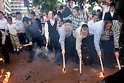 Young orthodox Jewish boys extinguishing their flame torches after a Sefer Torah procession with the new scroll to Kehal Chareidim Beth Hamedrash, an Ashkenazi synagogue in Stamford Hill.