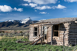 An old derelict log home from back in the settler days decays below the beautiful Mogg Mountain of the Lemhi Mountain Range