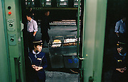 A busy platform with conductor and food vendor at a railway station in China