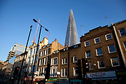 The Shard emerges from behind buildings on Borough High Street emphasising it's huge difference in scale and between the new and old architecture in London, UK.