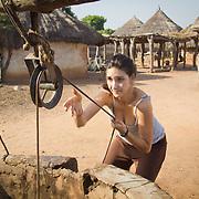 Peace Corps volunteer Rachael Honick hauls water from a well for her daily needs. Koumbadiouma, Kolda, Senegal.