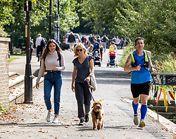 Licensed to London News Pictures. 15/09/2021. London, UK. Members of the public enjoy a walk along the Thames at Richmond, south west London as weather forcasters predict a warmer few days ahead with highs of 24c for London and the South East. Photo credit: Alex Lentati/LNP