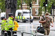 A member of the British army wearing face protective mask walks by the front door of UK Prime Minister's office as British authorities unboxed the Winston Churchill statue in Parliament Square in central London on Thursday, June 18, 2020, prior to a visit of the French President Emmanuel Macron to London. (Photo/ Vudi Xhymshiti)