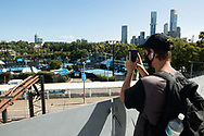 Tennis fans watch the only live tennis they can from a walkway over looking the outer courts a Melbourne Park. A snap lockdown has forced the Australian Open to be played with no crowds due to the entire state is returning to harsh stage-four lockdowns until Wednesday at 11.59pm as health authorities struggle to contain the Holiday Inn coronavirus outbreak.