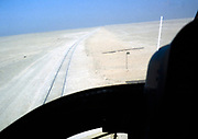 View from helicopter cockpit over railway line tracks in desert, Saudi Arabia 1979
