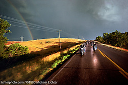 "After the Storm - Riding to the Drags in Belle Fourche, SD. 1980<br /> <br /> Limited Edition Print from an edition of 50. Photo ©1980 Michael Lichter.<br /> <br /> The Story: In 1979, there was flat track racing and hill climbs, but there was no drag strip in Sturgis.  If you wanted to see Pete Hill drag race his Knuckle, you had to ride to Belle Fourche.  It was questionable whether they would be racing on this day as the group of bikers mostly from Boulder left Sturgis' City Park campground.  Half way to the track, the skies began to clear.  A rainbow appeared just as the sun made the wet pavement and prairie grasses glow.  Free spirits crossed the ""Great West""."