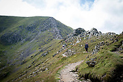 Walkers making their way along Swirral Edge between Helvellyn and Catstye Cam. The Lake District, Cumbria, United Kingdom on the 2nd of August 2021.