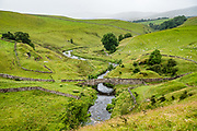 Old stone bridge. We hiked the valley of Smardale Gill to cross its historic Viaduct and visit Smardale Gill National Nature Reserve, in Yorkshire Dales National Park, England, United Kingdom, Europe. England Coast to Coast hike day 7 of 14; overnight 2 of 2 in Brownber Hall Country House, Cumbria county. [This image, commissioned by Wilderness Travel, is not available to any other agency providing group travel in the UK, but may otherwise be licensable from Tom Dempsey – please inquire at PhotoSeek.com.]