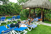 Relaxing in Bali. Look closely inside the hut . . . <br /> Kuta, Bali