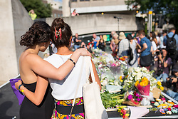 © Licensed to London News Pictures. 03/06/2018. London, UK. Members of the public embrace after laying flowers to mark one year since the London Bridge and Borough Market terror attacks. A series of events have taken place throughout the day, including a service of commemoration at Southwark Cathedral, the planting of an olive tree in the Cathedral grounds, a minute's silence at 4:30pm and the laying of flowers.  Photo credit : Tom Nicholson/LNP