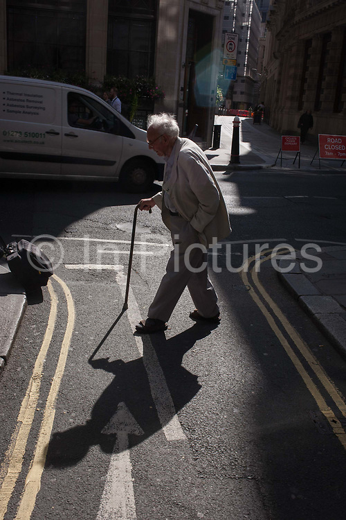 A frail, elderly man walks slowly with the help of a walking stick in sunlight, on 8th September 2016, in the City of London, England UK. Stepping carefully to cross the narrow street, an ancient path in the capitals financial district founded by the Romans in the first century.