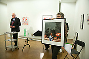 Auctioneer Chris Knapton going through the bids. The piece on sale is Photo Op, depicting former PM Tony Blair with burning oild wells behing him by artists kennardphillipps. In the back ground is a piece by Bob and Roberta Smith. Art auction held at Gimpel Fils in support of Ken Livingstone's bid for London Mayor in May 2012.