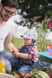 Father with his baby laughing and looking at a cherry on meadow in the countryside, Bavaria, Germany