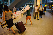 School musicians head for waiting coaches, one with a double-bass in Arrivals at Heathrow's terminal 5.