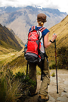 A female trekker looks down a valley on the Inca trail in the Peruvian Andes