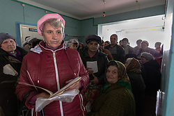 Patients , Vladimir Malishenko, (c at back) line up at the MSF mobile clinic in Bolshaya Vergunka, Lugansk,  to receive their prescribed medicines.