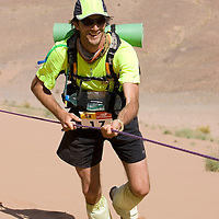26 March 2007:  #17 Emmanuel De Buchere de Lepinoit of France smiles as he reaches summit of jebel El Otfal, 947 meters and an average 25% slope, with the help of a cord, during the second stage (21.7 miles) of the 22nd Marathon des Sables between Khermou and jebel El Otfal. The Marathon des Sables is a 6 days and 151 miles endurance race with food self sufficiency across the Sahara Desert in Morocco. Each participant must carry his, or her, own backpack containing food, sleeping gear and other material.