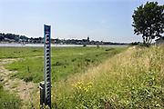 Nederland, Lent, Nijmegen, 26-6-2013 Een peilstok staat langs de Waal in de uiterwaarden. Bij 17 meter gaat het water de dijk over. In 1995 was de stand 16 meter 45. Om overstromingen te voorkomen en het water beter te laten doorstromen in de bocht bij deze stad wordt er een nevengeul aangelegd.Aan de overkant van de Waal bij Nijmegen wordt druk gewerkt aan het creeren van een nevengeul in de rivier om bij hoogwater een betere waterafvoer te hebben. Het is een omvangrijk project waarbij onder meer de pijlers van het spoorviaduct een bredere basis moeten krijgen omdat die straks in de loop van het water staan. Ook de n325 die vanaf de Waalbrug naar Arnhem loopt moet over 400 meter opnieuw worden aangelegd omdat het talud vervangen wordt door pijlers. De weg wordt via een bypass omgeleid. Het dorp veurlent komt op een kunstmatig eiland te liggen. Inmiddels begint de nieuwe kade aan de noordkant van deze geul vorm te krijgen. Ruimte voor de rivier, water, waal. In de nieuwe dijk wordt een drempel gebouwd die stapsgewijs water doorlaat en bij hoogwater overloopt. Measures taken by Nijmegen to give the river Waal, Rhine, more space to flow during highwater.Room, space for the river. Reducing the level, waterlevel.Foto: Flip Franssen/HollandseHoogte