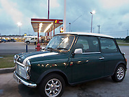 a classic Mini Cooper automobile is stopped at a gas station in Mississippi on a cross country trip.