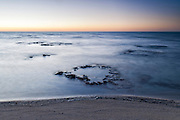Stromatolites peek above the Indian Ocean, Hamelin Pool, Australia