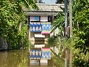 30 SEPTEMBER 2016 - SAI NOI, AYUTTHAYA, THAILAND: Drying laundry hangs from a home in Sai Noi, a flooded village on the Chao Phraya River. The Chao Phraya River, the largest river that runs through central Thailand, has hit flood stage in several areas in Ayutthaya and Ang Thong provinces. Villages along the river are flooded and farms are losing their crops due to the flood. This is the same area that was devastated by floods in 2011, but the floods this year are not expected to be as severe. The floods are being fed by water released from upstream dams. The water is being released to make room for heavy rains expected in October.      PHOTO BY JACK KURTZ