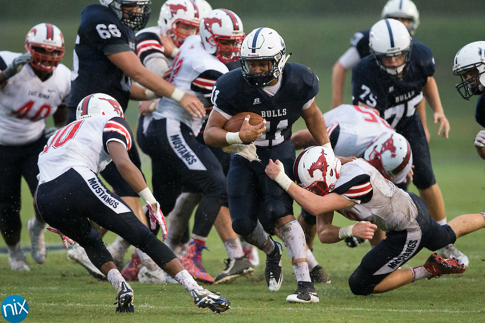 Jaylen Rudisell (11) of the Hickory Ridge Ragin' Bulls looks to avoid being tackled by the East Rowan Mustangs defense during first half action at Hickory Ridge High School on October 2, 2015 in Harrisburg, North Carolina.  The Ragin' Bulls defeated the Mustangs 20-7.  (Brian Westerholt/Special to the Tribune)