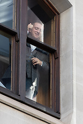 © Licensed to London News Pictures . 27/09/2018 . London , UK . TOMMY ROBINSON looks out of a second floor window of the Old Bailey and gives a thumbs up to supporting crowds on the street outside , ahead of the start of his retrial . Supporters of and those against former EDL leader Tommy Robinson (real name Stephen Yaxley-Lennon ) outside the Old Bailey , as Robinson faces a retrial for Contempt of Court following his actions outside Leeds Crown Court in May 2018 . Robinson was already serving a suspended sentence for the same offence when convicted in May and served time in jail as a consequence , but the newer conviction was quashed by the Court of Appeal and a retrial ordered . Photo credit: Joel Goodman/LNP