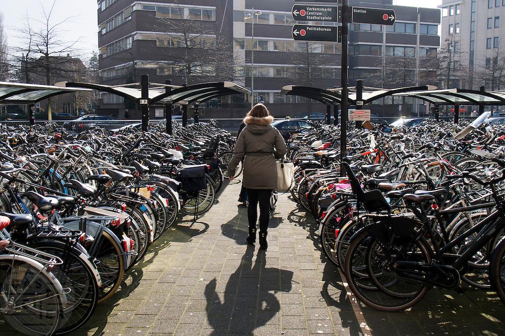 In Amersfoort loopt een vrouw tussen de overvolle fietsenrekken door voor het station.<br /> <br /> Amersfoort a woman walks among the crowded bike racks in front the train station.