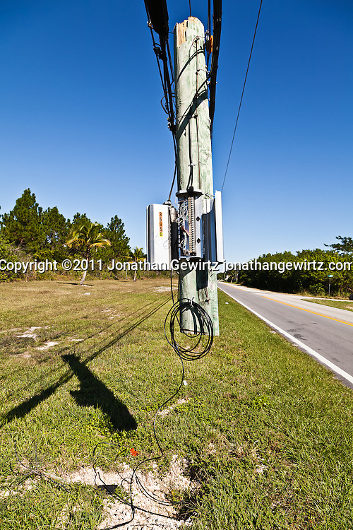 A wood utility pole whose top and bottom have been removed, hanging from utility wires and. WATERMARKS WILL NOT APPEAR ON PRINTS OR LICENSED IMAGES.