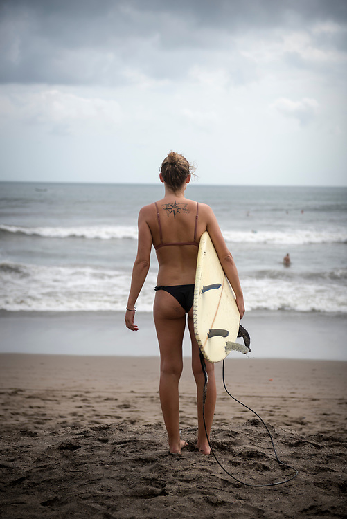Canggu, Bali, Indonesia - October 8, 2017: Fabienne, from Switzerland and with a world map tattooed on her back, holds a surfboard while looking out to the sea at the beach in Canggu, Bali.
