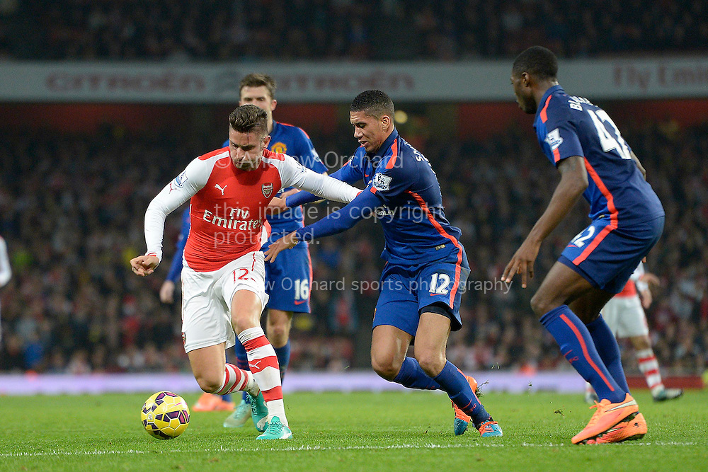 Olivier Giroud of Arsenal trying to break away from Chris Smalling of Manchester United. Barclays Premier league match, Arsenal v Manchester Utd at the Emirates Stadium in London on Saturday 22nd November 2014.<br /> pic by John Patrick Fletcher, Andrew Orchard sports photography.