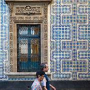 Couple walking past exterior wall of Casa de los Azulejos in Mexico City
