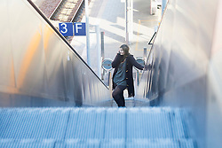 Young woman moving on escalator and talking on phone at railway station, Freiburg im Breisgau, Baden-Württemberg, Germany