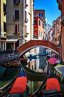 """""""Beautiful spring afternoon on the Rio del Frari - Venice""""...<br /> <br /> I am not sure if I am the first to describe Venice as """"organic""""; however, there has never been a more perfect description to define Venice's ever changing persona.  Venice is perhaps the most uniquely iconic seaside city in the world, and its impression changes by the minute with the ever changing light and active tide coming in and out.  Flying into Venice via the USA, I was met with torrential rains in the early morning, which finally gave way to afternoon sunshine.  The creaky, wet, gloomy, old, decaying Venice sinking and soaking in the morning rain… opened like flower petals in the springtime at first glimpse of sunlight.  The organic lagoon began to blossom as if the decay became antique, the gloom became passion, the creaky became sweet sounds, and the desperate island illuminated with life, color, and hope.  This image was taken along a small canal in front of The Santa Maria Gloriosa dei Frari (St. Mary of the Friars), known locally as Frari, one of the great churches of Venice.  Ironically, before my Italian journey, I read Rick Steves travel book on Italy and watched all of his shows made in Italy.  It seemed every American tourist had his book in their hands following closely every piece of advice he offered.  As I pondered my impending images, I looked up and there was Rick about 20 feet in front of me.  Sometimes one has moments of brilliance, and mine was to yell…""""hey Rick"""" and snap a photo when he looked.  He actually smiled as I walked up and shook his hand, and dumbfoundedly I shared how much he contributed to my trip.  He was very gracious as we spoke for about five minutes and then he continued producing his next PBS show on the Venice Lagoon including his favorite church, Frari.  As I walked away shocked by my accidental meeting, the clouds parted and the light struck a perfect note along this tiny majestic canal."""