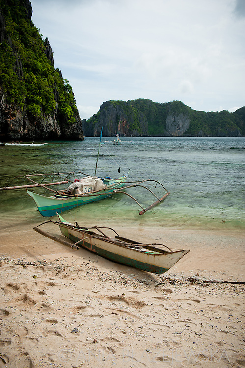 Philippines, Palawan. Local bangkas (traditional boats) at the shore of a small island in Bacuit Archipelago.