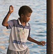Boy throws stones at a floating target on the waterfront in Port Vila, Vanuatu.